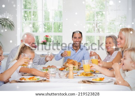 Composite image of Family toasting at thanksgiving against snow falling - stock photo