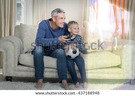 Composite image of father and son are watching sport match on television at home - stock photo