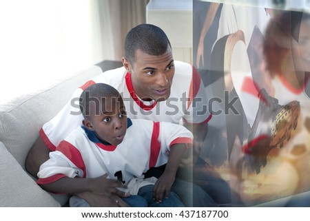 Composite image of father and son are watching sport on television at home - stock photo