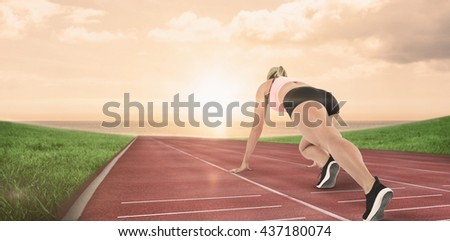 Composite image of female athlete on the start line on a race track