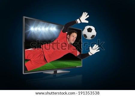 Composite image of fit goal keeper saving goal through tv against football pitch under spotlights - stock photo