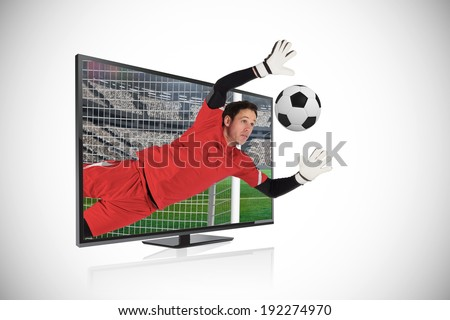 Composite image of fit goal keeper saving goal through tv against white background with vignette - stock photo