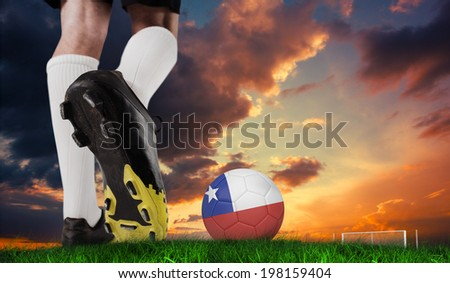 Composite image of football boot kicking chile ball against green grass under dark blue and orange sky