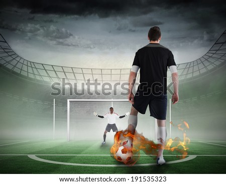 Composite image of football player about to take a penalty against football pitch in large stadium
