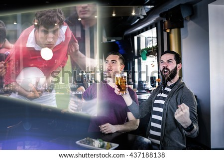 Composite image of friends are watching rugby match in a pub