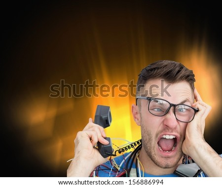 Composite image of frustrated computer engineer screaming while on call on black glowing background - stock photo