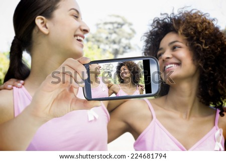 Composite image of hand holding device showing photograph of breast cancer activists - stock photo