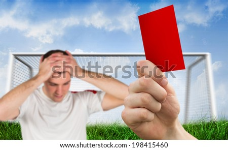 Composite image of hand holding up red card to player against goalpost on grass under blue sky - stock photo