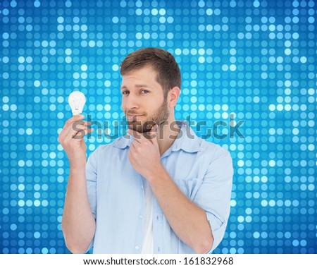 Composite image of handsome model holding a bulb  - stock photo