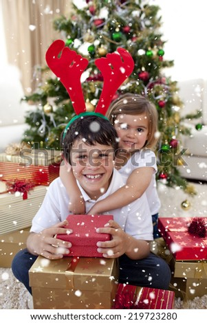Composite image of Happy brother and sister celebrating Christmas with snow falling - stock photo