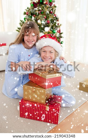 Composite image of Happy brother and sister holding Christmas presents with snow falling - stock photo