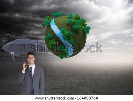 Composite image of happy businessman holding grey umbrella - stock photo