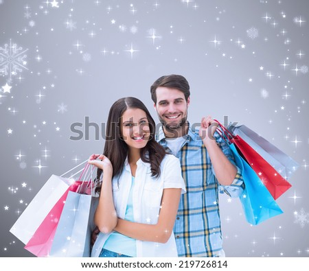 Composite image of happy couple with shopping bags against grey vignette - stock photo
