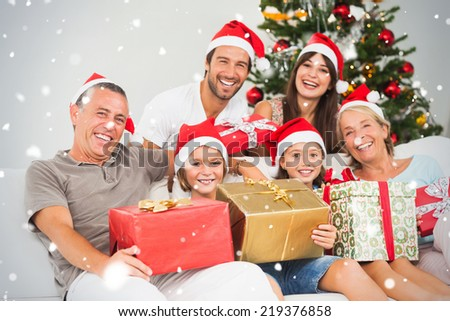 Composite image of Happy family at christmas holding gifts against snow falling