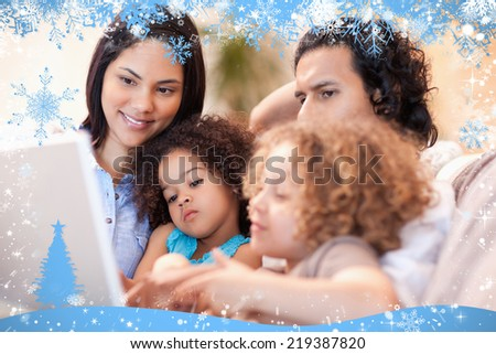 Composite image of happy family using laptop together against snow - stock photo