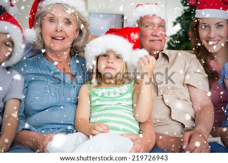 Composite image of Happy multigeneration family wearing santa hats on the couch against snow falling