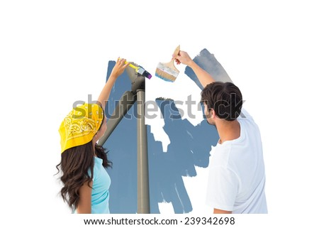 Composite image of happy young couple painting a sky on white wall - stock photo