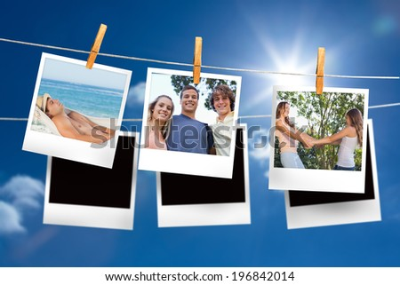 Composite image of instant photos hanging on a line against blue sky - stock photo