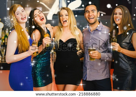Composite image of Laughing friends holding beers posing against snow falling - stock photo