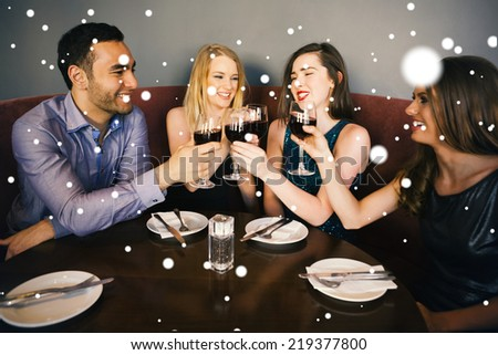Composite image of Laughing friends sitting together clinking glasses against snow - stock photo