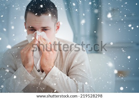 Composite image of man blowing his nose against snow falling - stock photo