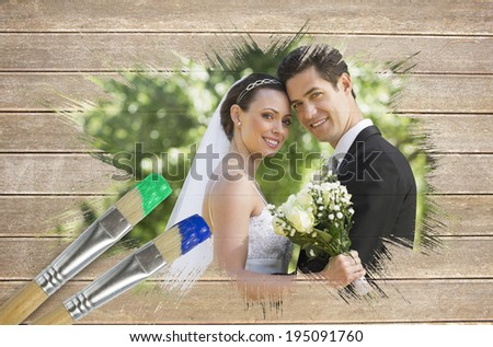 Composite image of newlyweds smiling at camera with paintbrush dipped in blue against wooden surface with planks - stock photo