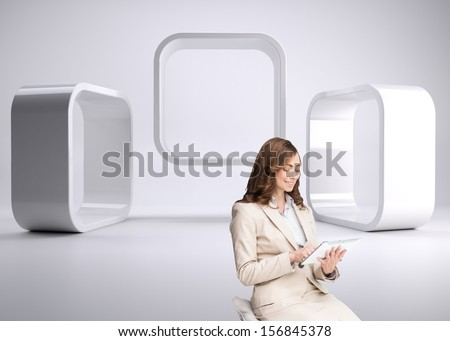 Composite image of pleased businesswoman using a tablet pc sitting on a bar chair in front of 3d squares