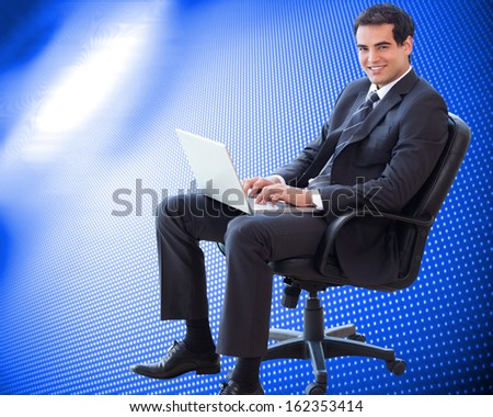 Composite image of portrait of a young businessman sitting on an armchair working with a laptop - stock photo