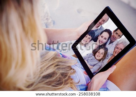 Composite image of portrait of family on sofa - stock photo