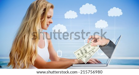 Composite image of pretty blonde using her laptop at the beach with hand holding money - stock photo