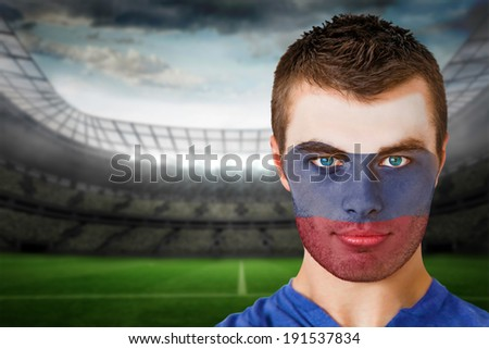 Composite image of russia football fan in face paint against large football stadium with lights - stock photo
