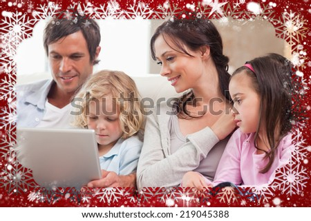 Composite image of serene family using a notebook against snow - stock photo