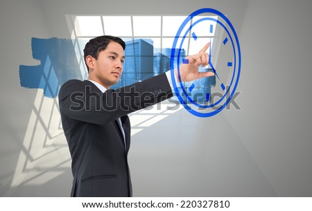 Composite image of serious asian businessman pointing to a clock - stock photo