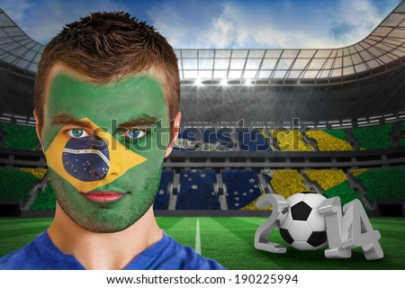 Composite image of serious young brasil fan with face paint against large football stadium with brasilian fans - stock photo