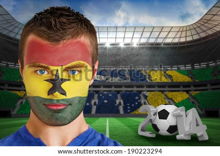 Composite image of serious young ghana fan with face paint against large football stadium - stock photo