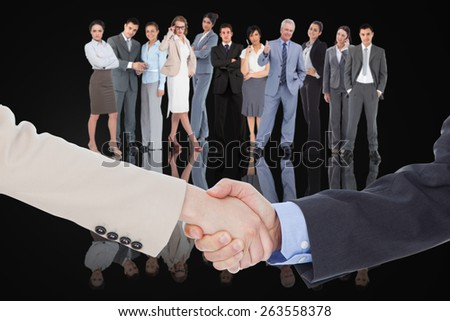 Composite image of smiling business people shaking hands while looking at the camera - stock photo