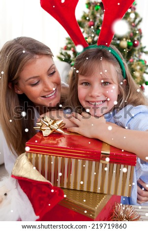Composite image of Smiling mother and her daughter holding Christmas gifts with snow falling - stock photo