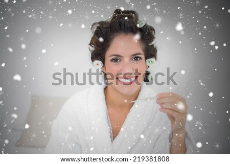 Composite image of smiling natural brunette holding thermometer against snow falling - stock photo