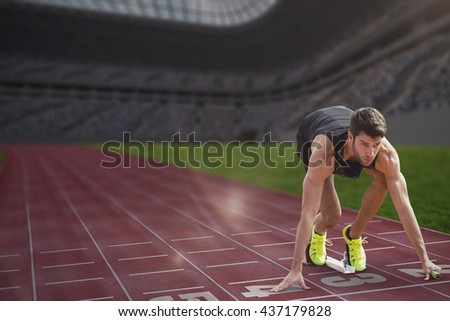 Composite image of sportsman waiting on the starting block in a stadium - stock photo