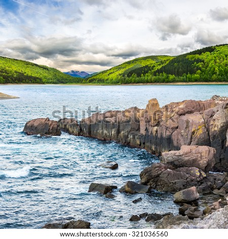 composite image of summer landscape  on lake with rocky shore and some boulders near forest in mountain  with high peak far away in morning light - stock photo