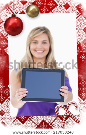Composite image of Tablet computer being held by a blonde woman with christmas themed page - stock photo