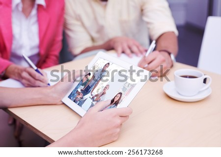 Composite image of team having meeting and smiling at camera - stock photo