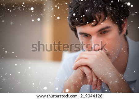 Composite image of thoughtful man in the living room against snow - stock photo