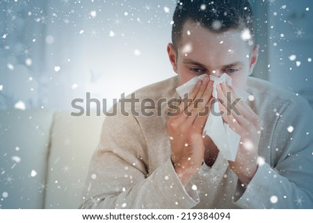 Composite image of tired man blowing his nose against snow falling - stock photo