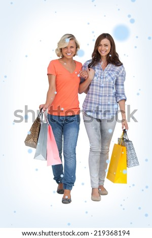 Composite image of Two cheerful friends with shopping bags with snow falling - stock photo