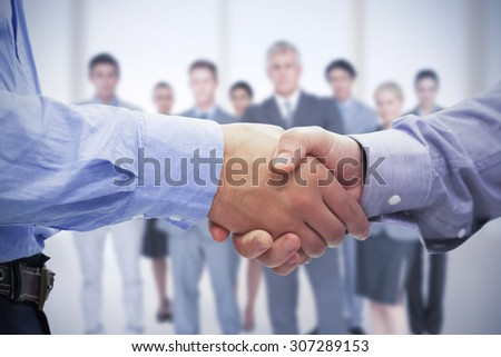 Composite image of two men shaking hands