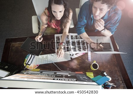 Composite image of website interface against colleagues using a graphic pad - stock photo