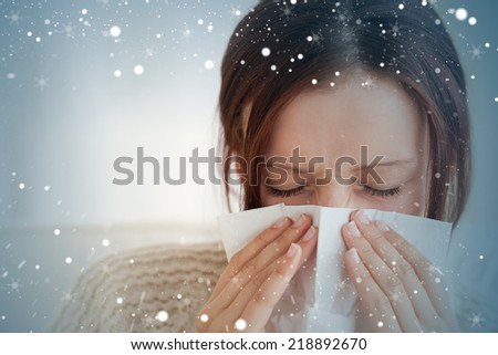 Composite image of woman blowing her nose against snow - stock photo