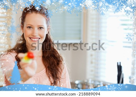 Composite image of woman offering some salad against snow - stock photo