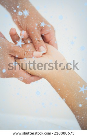 Composite image of Woman receiving a hand massage with snow falling